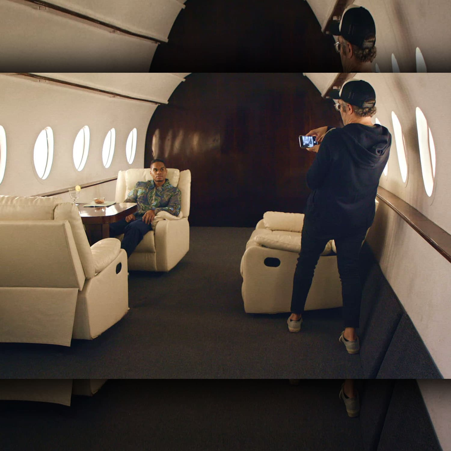 "Journalist Nick Bilton takes a photo of Chris Bailey on a fake private plane set for the HBO documentary ""Fake Famous.""Source: HBO"